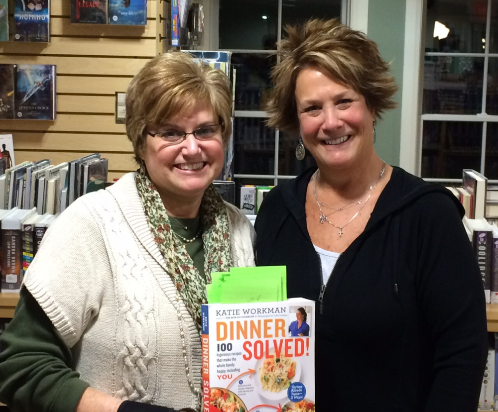 "Springvale Public Library assistant director Dawn Brown, left, and Cook the Book Club member Mary Ann Ratteree with ""Dinner Solved!"" by Katie Workman, the first cookbook the group tested recipes from and reviewed."