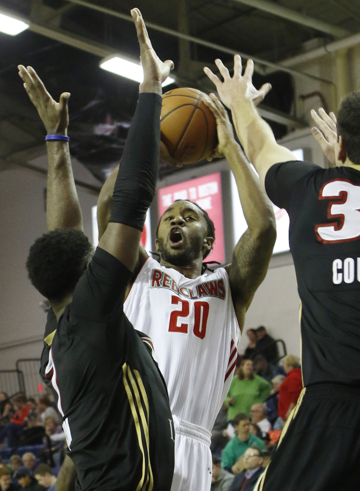 Maine's Levi Randolph, center, takes a shot while being defended by Erie's Melvin Ejim, left, and Daniel Coursey during the Red Claws' 110-97 win Sunday.