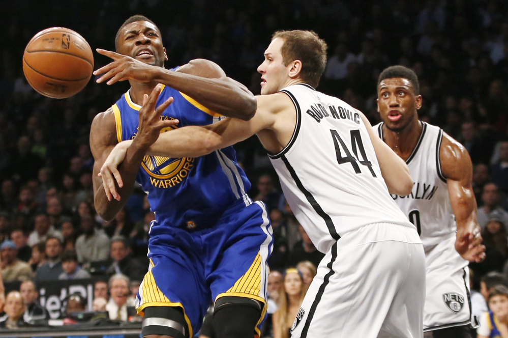 Nets guard Bojan Bogdanovic, right, fouls Warriors center Festus Ezeli in the first half Sunday in New York. The Warriors won their 26th straight regular-season game.