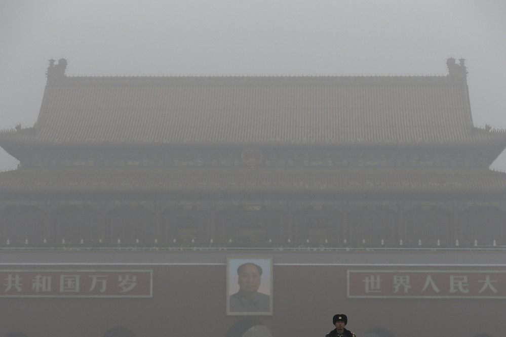 A paramilitary police officer stands guard near Tiananmen Gate shrouded with heavy pollution and fog in Beijing, China on Tuesday, Dec. 1, 2015. Schools in the capital kept students indoors and parents brought their kids to hospitals with breathing ailments Tuesday as Beijing grappled with extremely severe air pollution for the fifth straight day.