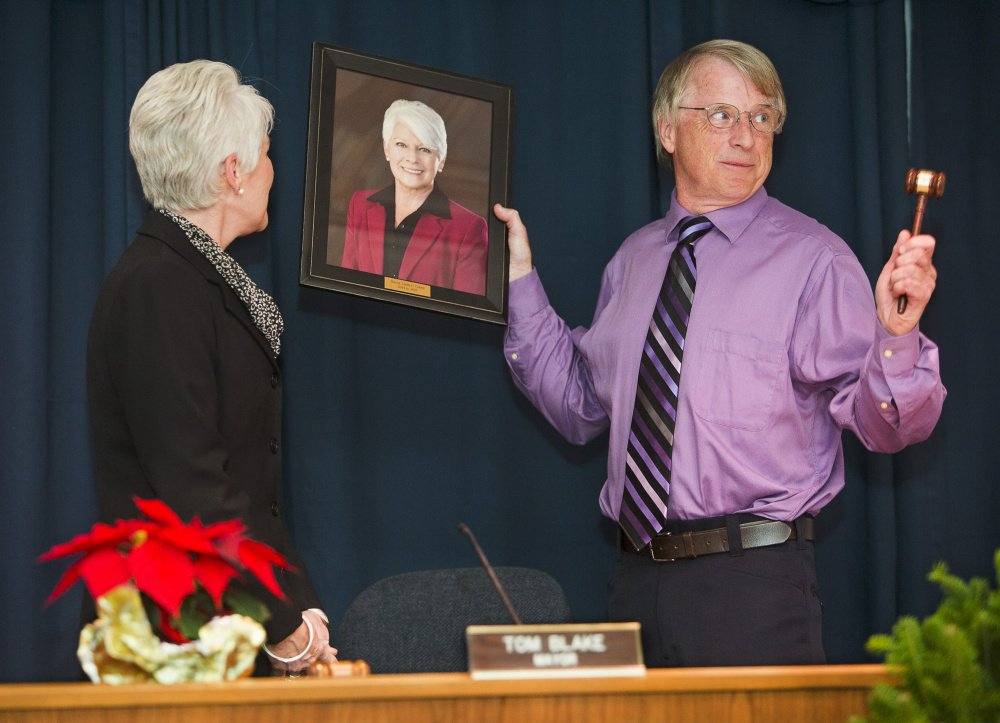 Newly inaugurated Mayor Tom Blake presents outgoing Mayor Linda Cohen with a gavel and a framed portrait after succeeding her at Monday evening's inaugural ceremony at City Hall.