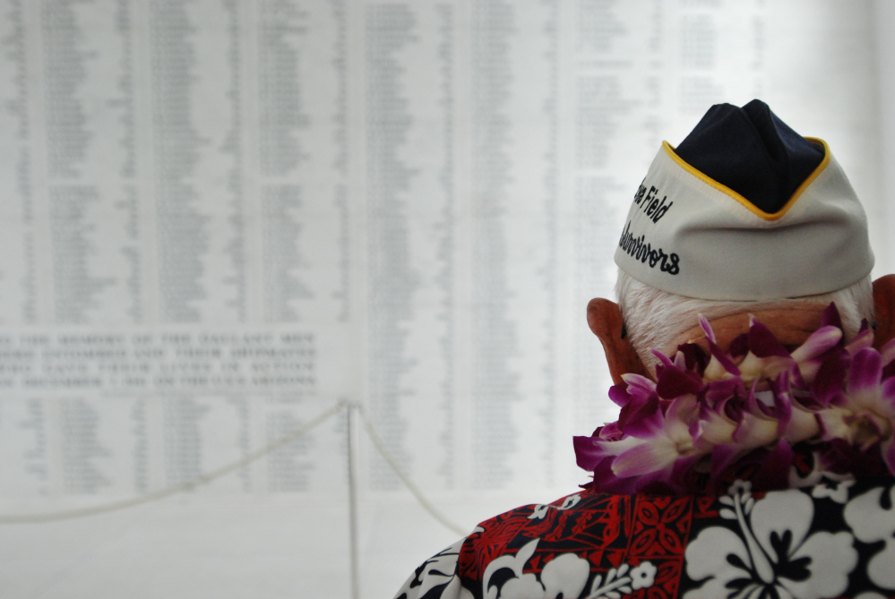 Pearl Harbor survivor John Hughes views a wall engraved with the names of USS Arizona sailors and Marines killed in the Japanese attack on Pearl Harbor.