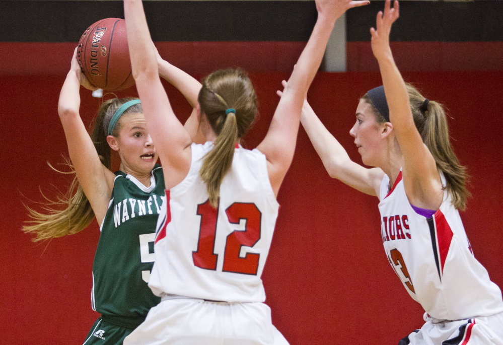 Waynflete guard Izzy Burdick is pressured by Wells guard Ally O'Brien and forward Megan Schneider during the Warriors' 47-28 win Monday in Wells.