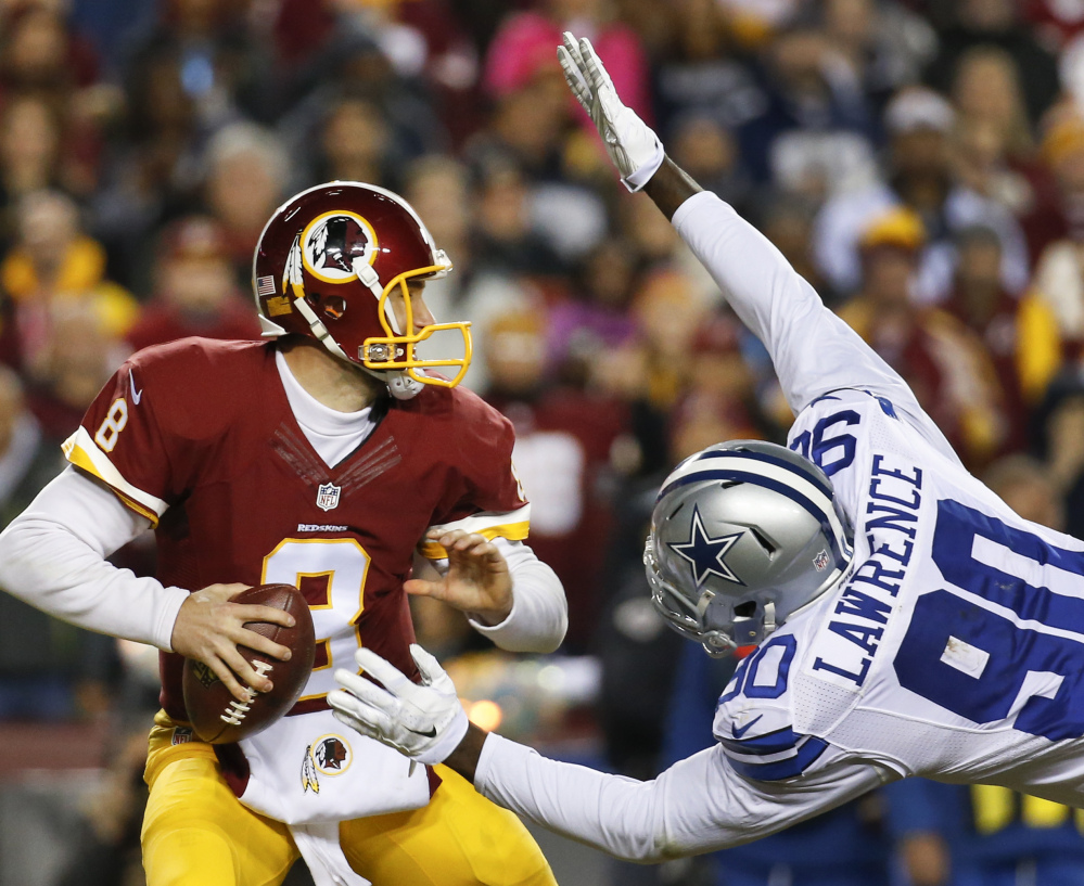 Cowboys defensive end Demarcus Lawrence leaps at Washington quarterback Kirk Cousins for a sack during the first half of their game Monday in Landover, Maryland.