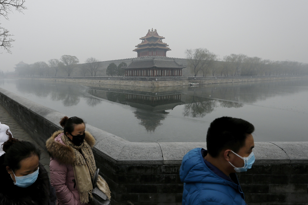 People wearing masks walk past the Turret of the Forbidden City on a heavily polluted day in Beijing Tuesday.