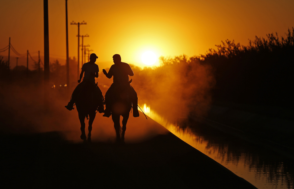 Two men ride on horseback along an irrigation canal in agricultural land near Modesto, Calif.