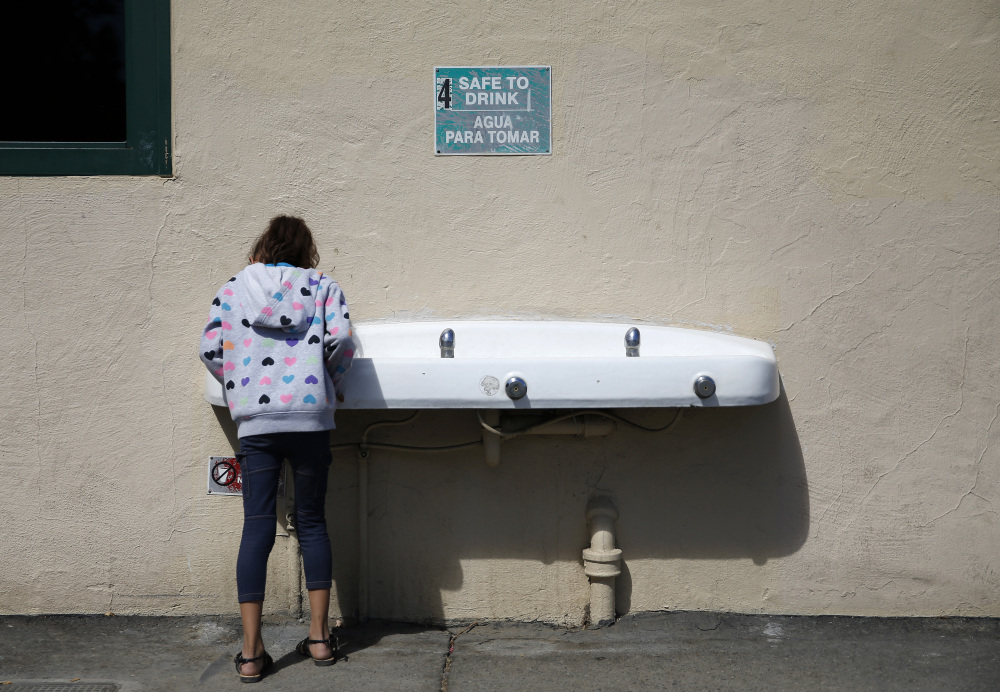 A student drinks from a water fountain below a sign signaling the water as safe to drink at Westport Elementary School in Ceres, Calif.