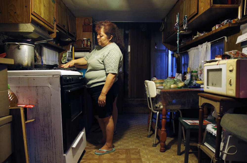 Dora Martinez cooks food at her home in a trailer park near Fresno, Calif.