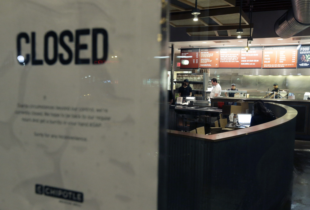 People stand inside a closed Chipotle restaurant on Monday, in the Cleveland Circle neighborhood of Boston.