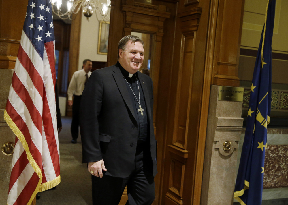 Indianapolis Archbishop Joseph Tobin leaves the governor's office after a meeting with Indiana Gov. Mike Pence at the Statehouse, Wednesday, Dec. 2, 2015, in Indianapolis, the day after the archdiocese said it has the means to resettle a Syrian refugee family bound for the state.