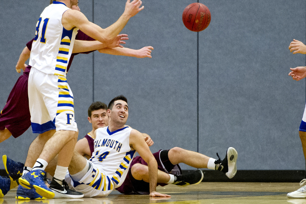 Justin Guerette and Thomas Coyne of Falmouth look on from the floor after as their teammates fight for possession of the ball before it bounces out of bounds. Gabe Souza/Staff Photographer