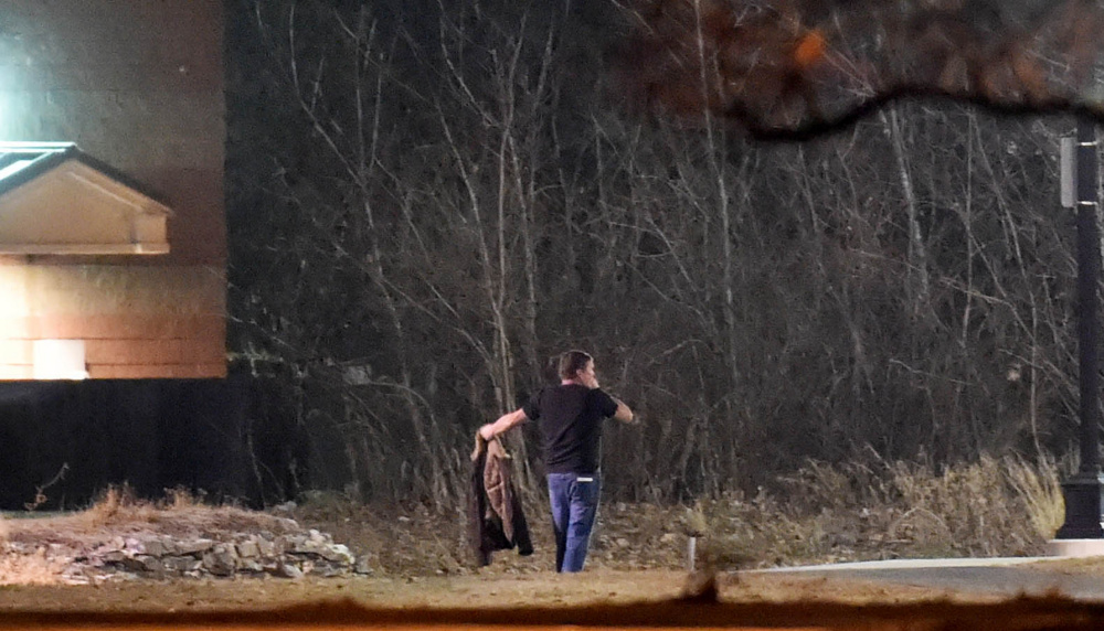A man, later identified as Gary Cross of Troy, walks toward police with his arms extended as he surrenders Tuesday morning after a standoff at the Waterville Police Department.