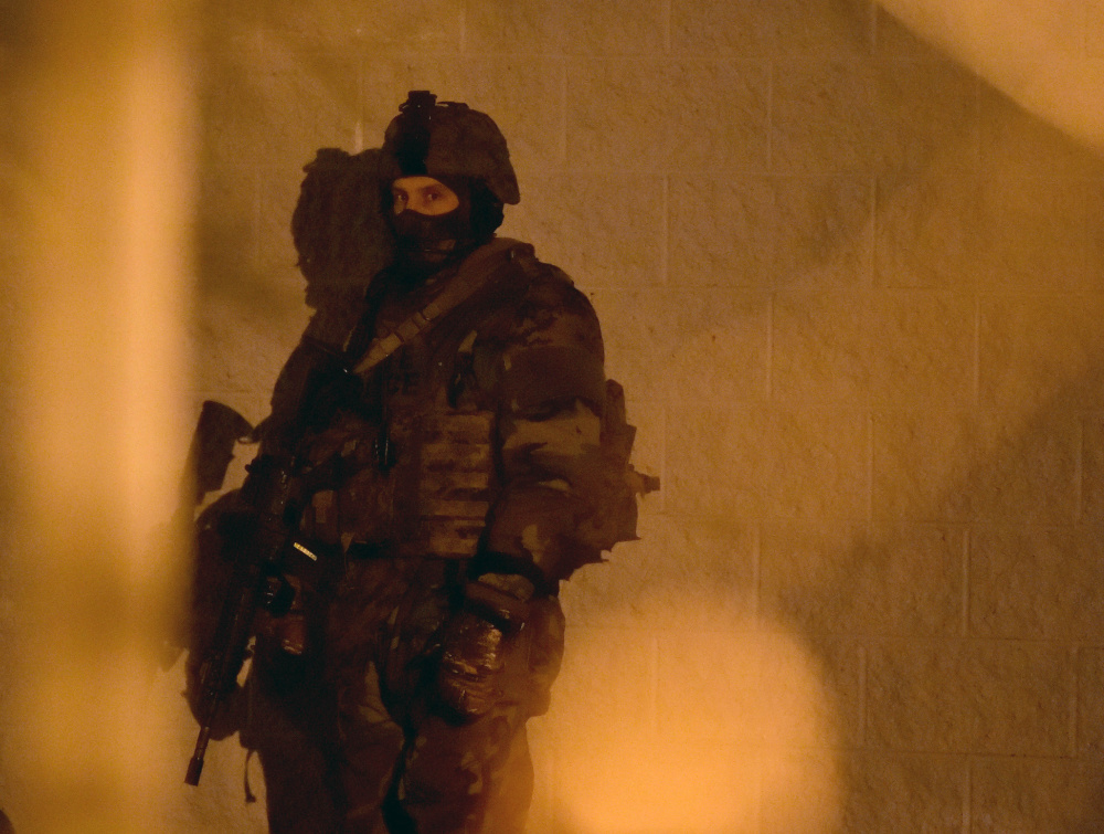 A member of the Maine State Police tactical team stands ready Tuesday during a standoff at the Waterville Police Department.