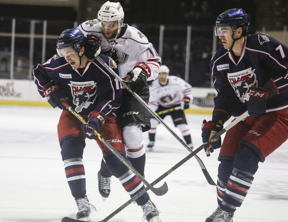 Pirates center Rob Schremp dives atop Springfield Falcons left wing Dan O'Donoghue while defender Steven Delisle watches the goal at the Cross Insurance Arena in Portland on Wednesday.