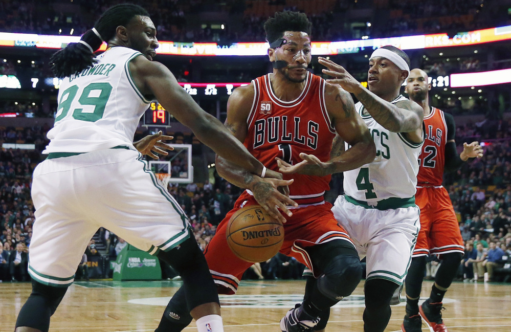 The Bulls' Derrick Rose loses control of the ball as he tries to drive between the Celtics' Jae Crowder and Isaiah Thomas in the first quarter of the Celtics' win on Wednesday night in Boston. Thomas led the Celtics' scoring with 20 points.