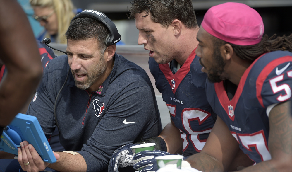 Mike Vrabel, left, linebackers coach for the Houston Texans, talks with Brian Cushing, center, and Justin Tuggle during a game on Oct. 18. Vrabel has long shown an interest in coaching, dating to his time as a linebacker with the Patriots.