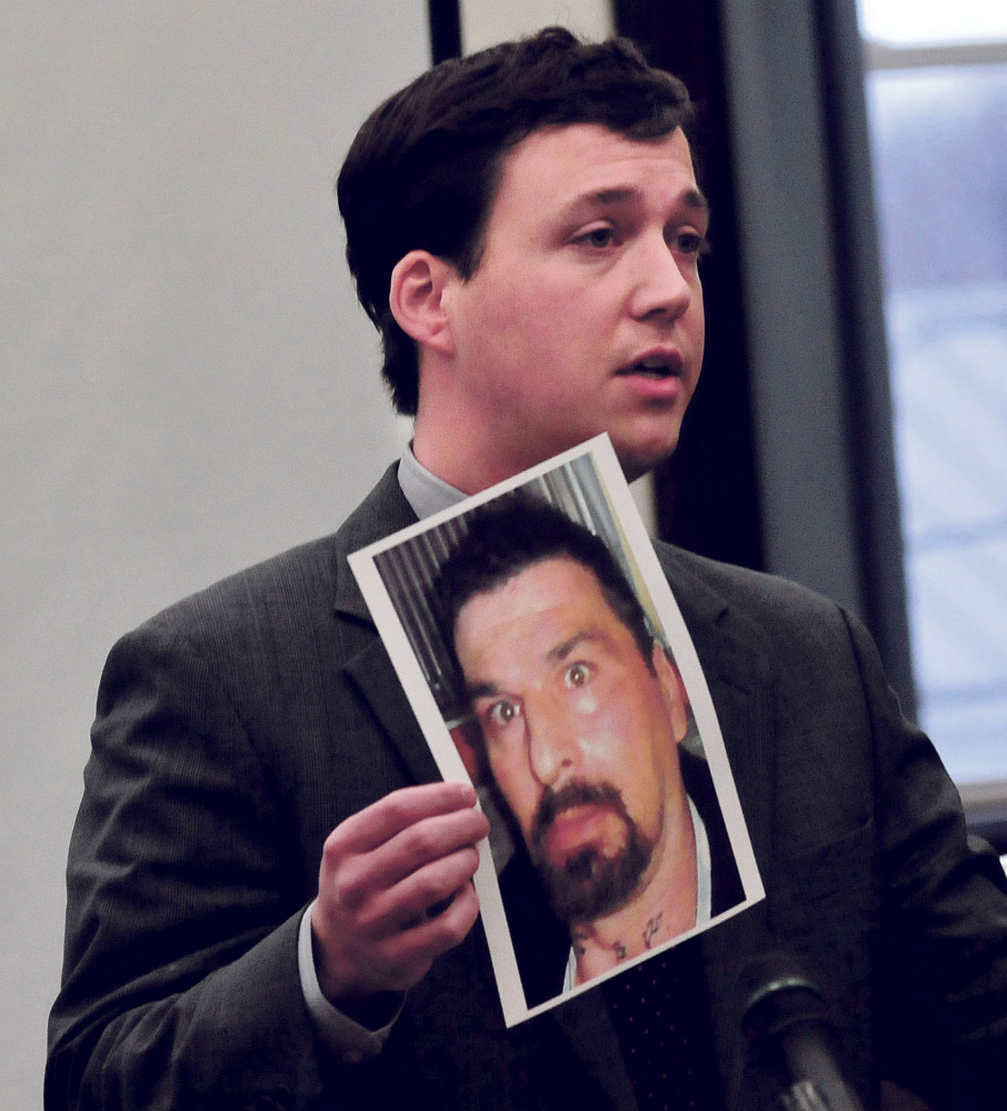 Defense attorney Caleb Gannon holds a photograph of Ricky Cole, who was killed in 2013, during the first day of trial of Jason Cote, of Palmyra, on Thursday in Somerset County Superior Court in Skowhegan.