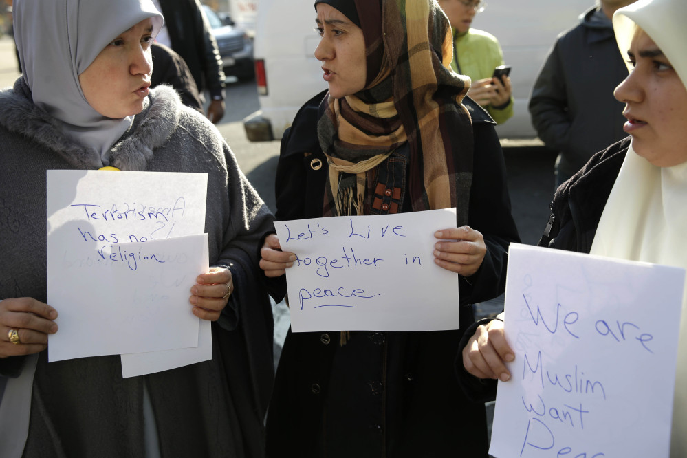 Amina Ismail, left, Fatima Amaziane, center, and Dalia Abdallah hold signs during a news conference in the Queens borough of New York on Thursday to express opposition to hate crimes and rhetoric, particularly in light of a recent attack in the neighborhood that police are investigating as a hate crime.