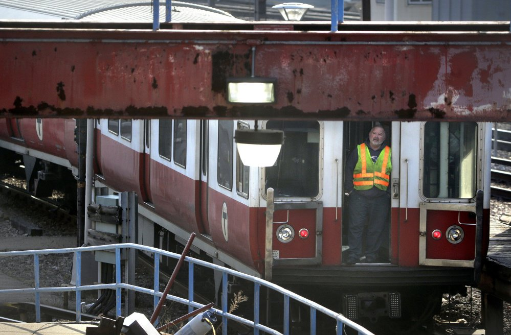 A worker stands at an entrance to a six-car train in Boston that earlier left a suburban transit station without a driver. The train went through four stations before being stopped.