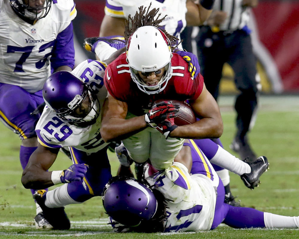 Arizona Cardinals wide receiver Larry Fitzgerald tries to surge forward as he is hit by Minnesota defenders Xavier Rhodes, left, and Anthony Harris on Thursday. Arizona kicked a field goal in the final minutes for a 23-20 win and improved to 11-2 on the season.