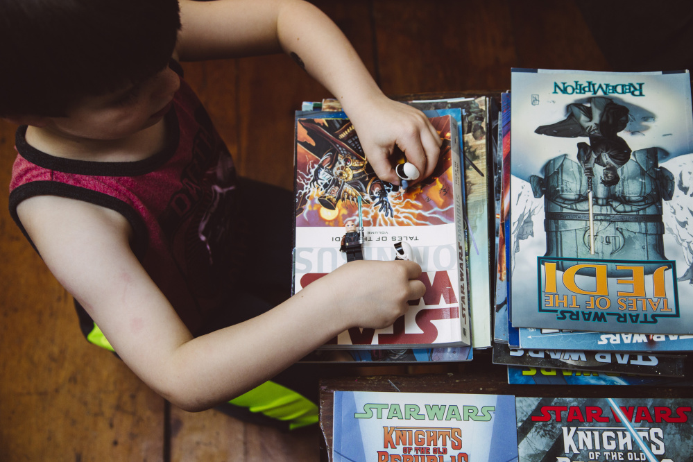 SOUTH PORTLAND, ME - DECEMBER 2: Abraham Irvine, (cq)  5, plays with Star Wars legos atop a collection of Star Wars graphic novels at their home in South Portland, ME on Wednesday, December 2, 2015. (Photo by Whitney Hayward/Staff Photographer)