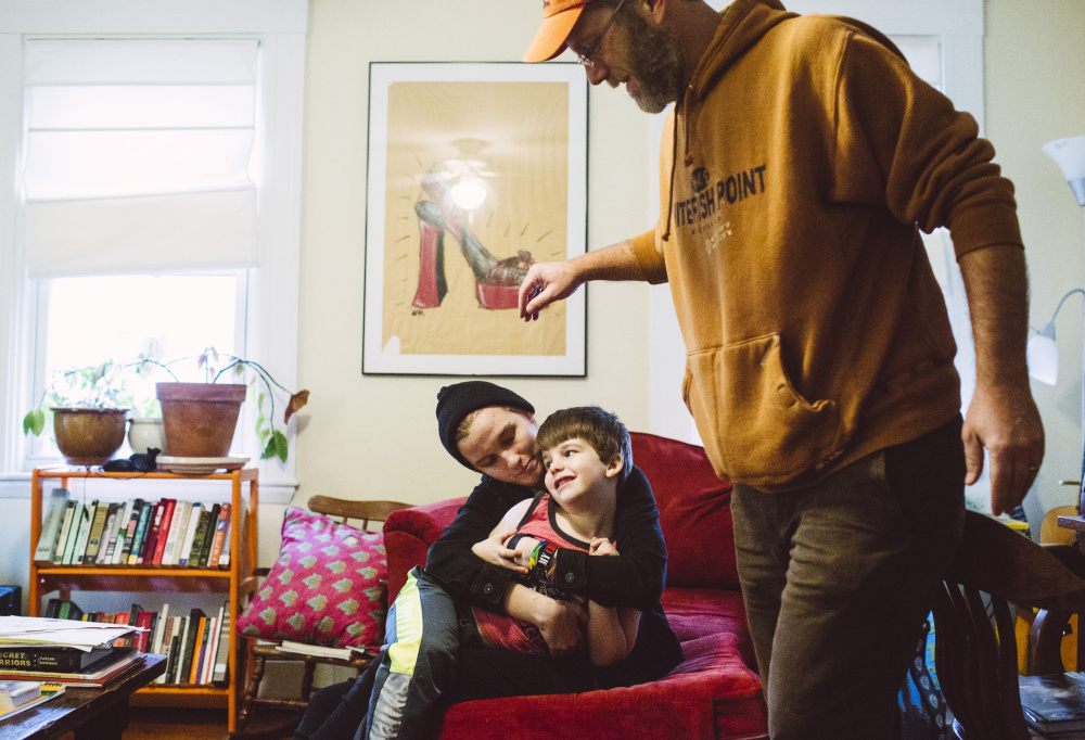 Emma Irvine, 14, holds her brother Abraham Irvine 5, with their father Alex Irvine at their home in South Portland. Irvine is a science fiction writer, along with a Star Wars fan, and he's passed down a love for both to his three children.