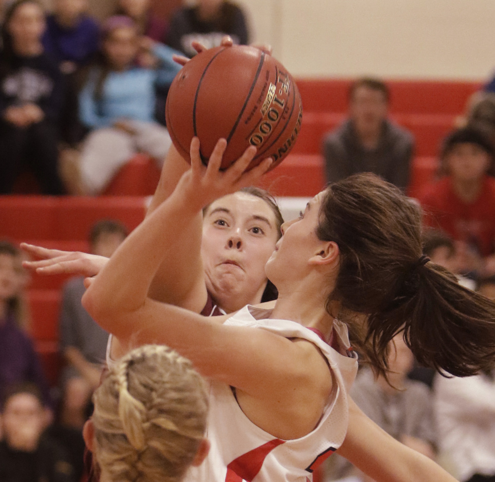 Mackenzie Holmes of Gorham blocks a shot by South Portland's Maddie Hasson during a Class AA South girls' basketball game Friday in South Portland. Gorham improved to 3-0 with a 40-38 victory.
