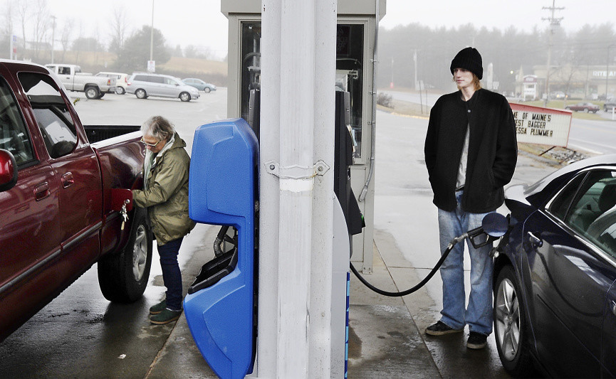 "Jane Brown, left, from Standish and Aaron LeConte of Buxton fill their tanks with gas for $2 a gallon at the Sunoco gas station in Buxton. ""I was a little boy the last time gas was this low,"" LeConte said."