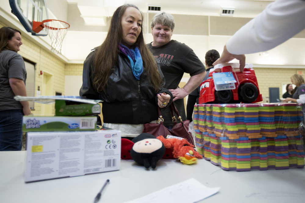 Jeannette Burns of Portland picks up toys for her five grandchildren at the Salvation Army's annual toy distribution program Thursday. Yoon S. Byun/Staff Photographer