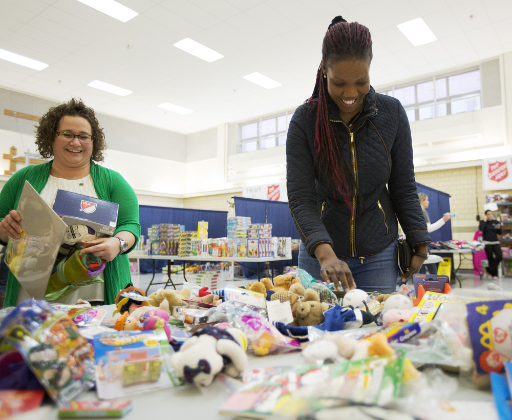 Viola Lupai looks through stuffed animals at the Salvation Army's toy distribution program, funded by kettle donations, as volunteer Jessica Nason helps her. The Salvation Army raised its fundraising goal this year to meet needs in Maine.