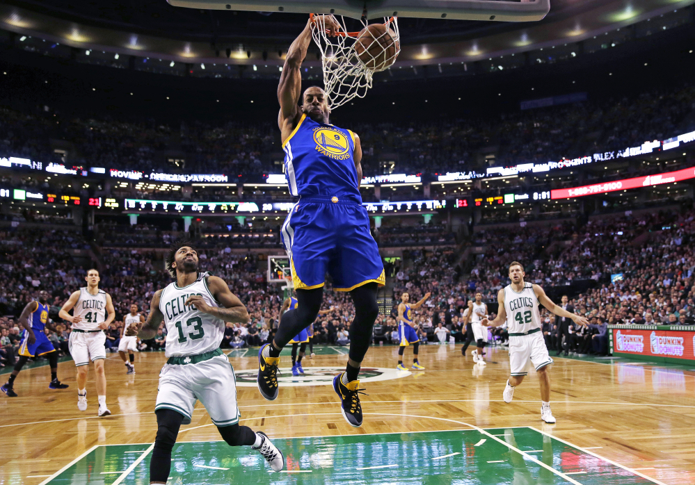 Warriors forward Andre Iguodala slams a dunk over Celtics guard James Young in the first quarter of what turned out to be a very long game – and a Warriors win.