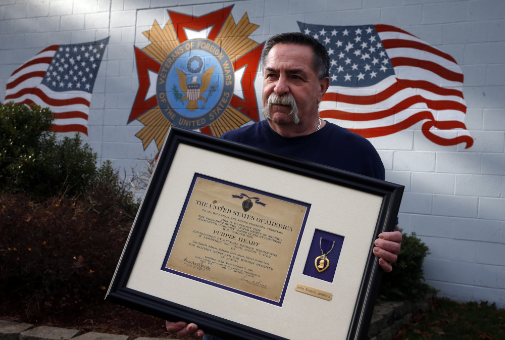 Jim Doherty, 66, of Holbrook and post commander of VFW Post 1046, holds the Purple Heart found by a teenage girl inside the Brockton (Mass.) VFW Post. (Jessica Rinaldi/The Boston Globe via AP)