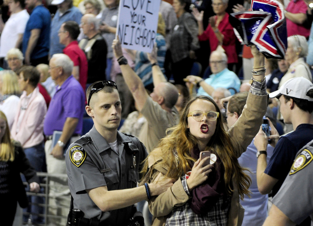 """Protester Sarah Villafañe is escorted from a Donald Trump rally in Aiken, S.C., on Saturday after the candidate's supporters chanted """"Trump! Trump! Trump!"""" to alert security personnel of a vocal dissident."""