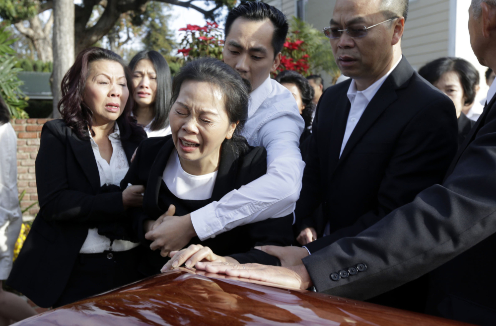Trung Do embraces his mother Van Thanh Nguyen, center, who weeps over daugther Tin Nguyen's coffin during Friday services in Westminster, Calif.