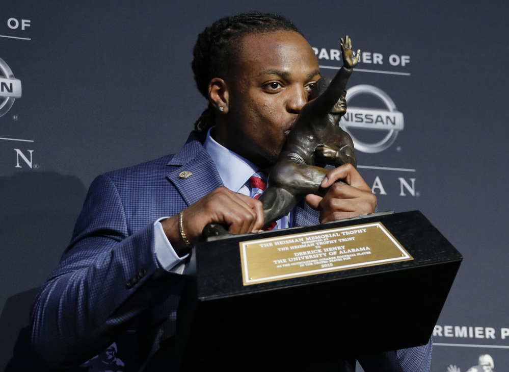 Alabama's Derrick Henry kisses the Heisman Trophy while posing for photos after winning the award as the country's top college football player Saturday in New York.