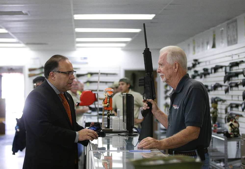 Sales associate Mike Conway, right, shows Paul Angulo a semiautomatic rifle at Bullseye Sport gun shop in Riverside, Calif.