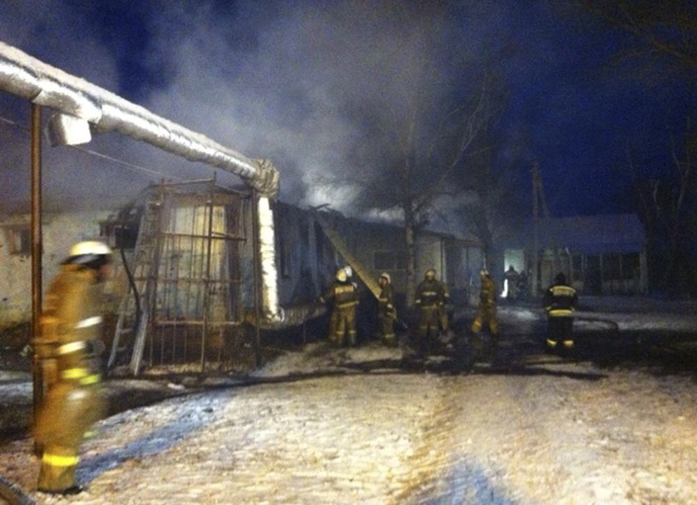 Firefighters work to put out a blaze at a Russian home for people with mental illness in Alferovka, about 350 miles south of Moscow. Russian emergency services say 23 people died.