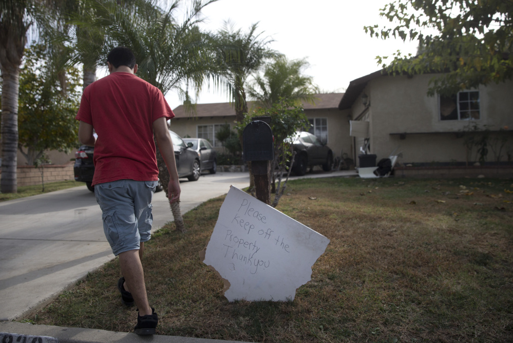A brother of Enrique Marquez walks toward the family home on Wednesday in Riverside, Calif. Investigators are trying to piece together what Marquez knew about the San Bernardino attacks.