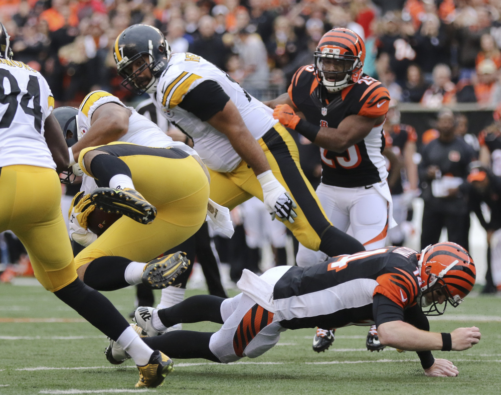 Steelers defensive end Stephon Tuitt gets tripped up by Bengals quarterback Andy Dalton after an interception Sunday. Dalton broke the thumb on his throwing hand.
