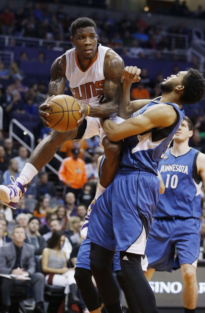 Eric Bledsoe of the Suns looks to make a pass while being defended by Minnesota's Karl-Anthony Towns during the Suns' 108-101 win Sunday in Phoenix.