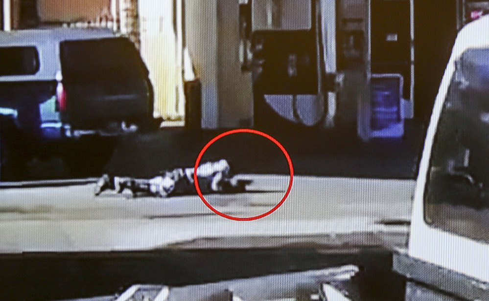 Nicholas Robertson is stretched out on the ground with a gun in his hand after he was shot by sheriff's deputies Saturday. The deputies fired at Robertson more than 30 times.