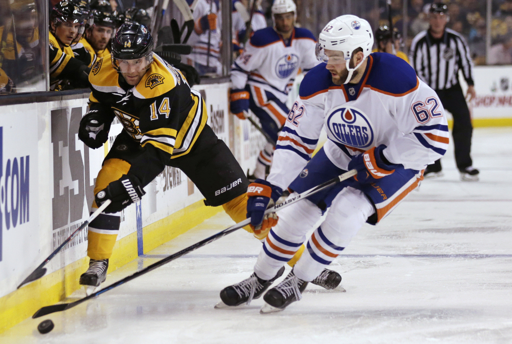 Oilers defenseman Eric Gryba strips the puck from Bruins right wing Brett Connolly in the second period of Edmonton's overtime win Monday night in Boston.
