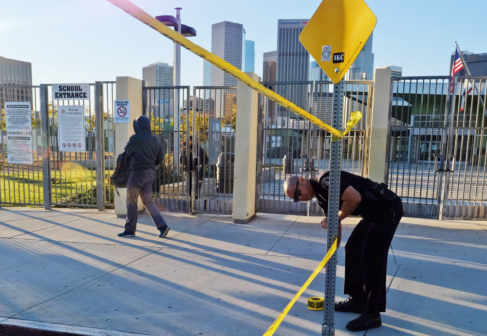 A police officer puts up yellow tape to close the school as a student walks past Edward Roybal High School in Los Angeles on Tuesday.