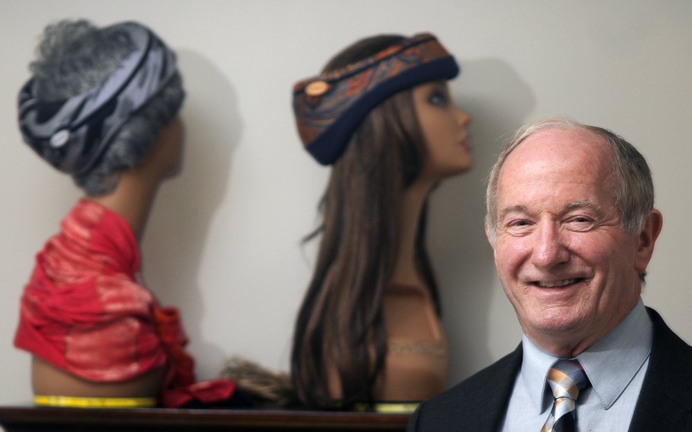 Alba-Technic co-founder Jim Ferguson poses with mannequins adorned with Smarty head gear Tuesday at the company's office in Winthrop. The head injury prevention attire helped make Alba-Technic one of five companies across the country to receive $250,000 from the NFL, Under Armour and the federal government to advance technology for safer sports equipment.