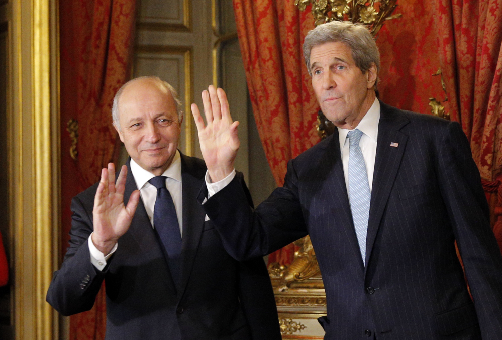 U.S. Secretary of State John Kerry, right, and  French foreign minister Laurent Fabius greet the media before a meeting in Paris on Monday. The Associated Press
