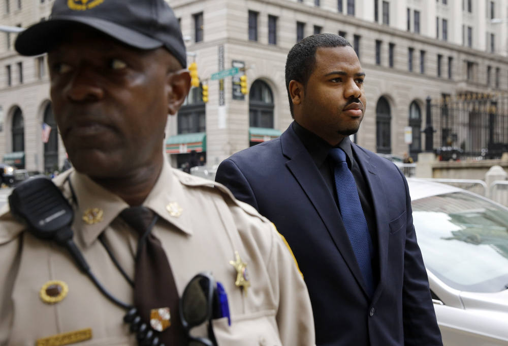 Officer William Porter, right, one of six Baltimore police officers charged in the death of Freddie Gray, walks into the courthouse during jury deliberations Wednesday in Baltimore. Jurors could not reach a verdict in the case so the judge declared a mistrial.