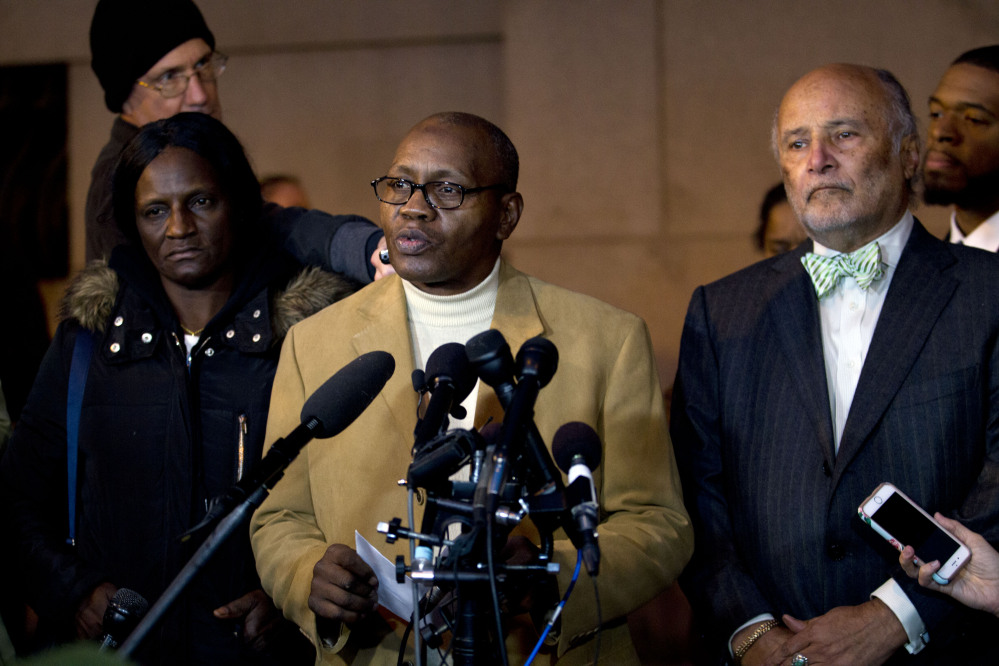 Freddie Gray's stepfather, Richard Shipley, center, with Gray's mother, Gloria Darden, and lawyer Billy Murphy, speaks to the media after a mistrial was declared Wednesday in the manslaughter trial of Officer William Porter. Officials appealed for calm as small crowds protested after the mistrial was declared.