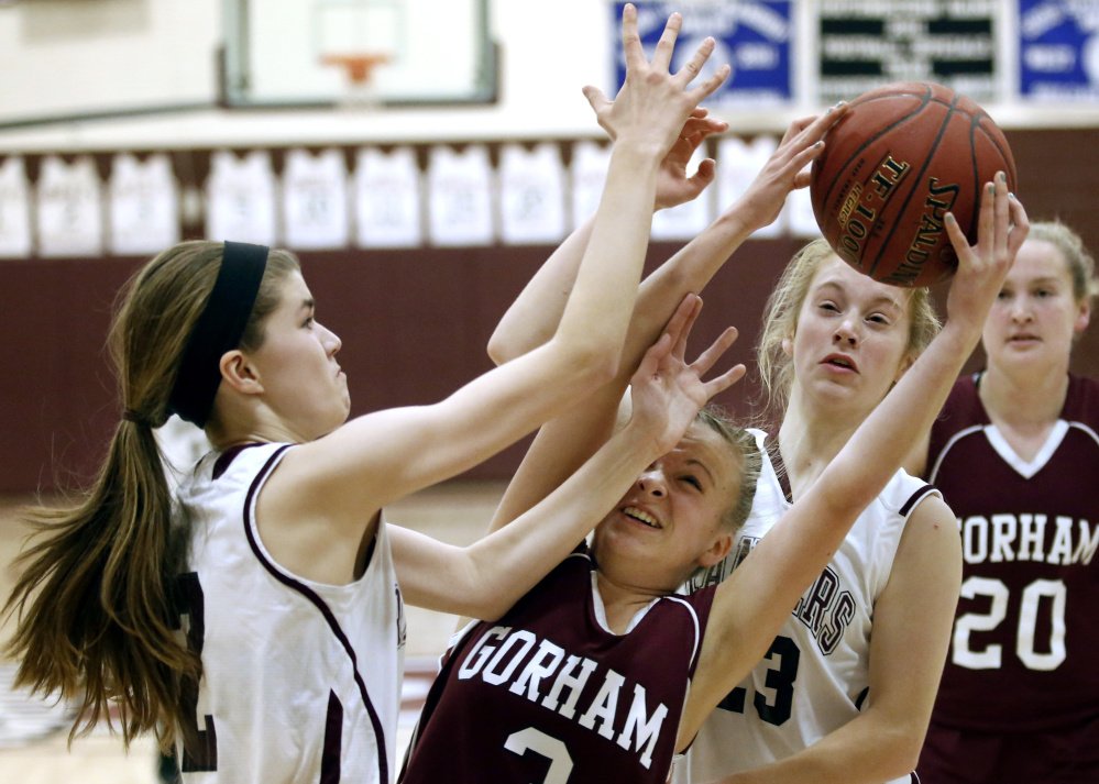 Kaylea Lundin, whose late 3-pointer put away the victory for Gorham, is in the middle of a rebound tussle Wednesday night with Isabel Porter, left, and Anna DeWolfe of Greely. Gorham reached 5-0 by holding on for a 57-49 victory.