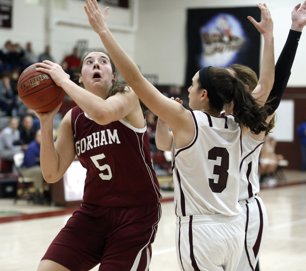 Mackenzie Holmes of Gorham focuses on the basket while shooting over Moira Train, right, and Maddie Cyr of Greely. Holmes scored her 12 points in the first quarter for the Rams.