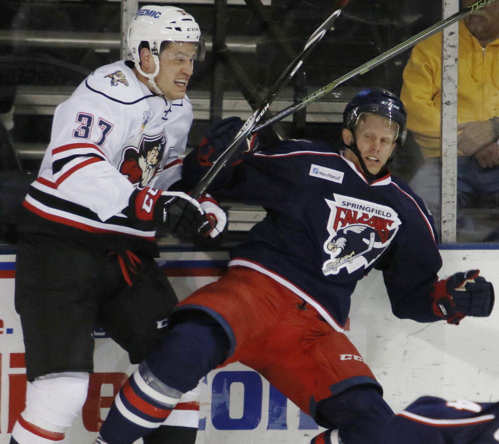 Tony Turgeon of the Portland Pirates, left, checks Philip Samuelsson of the Springfield Falcons into the boards Wednesday night during the second period of Portland's 5-2 victory at the Cross Insurance Arena.